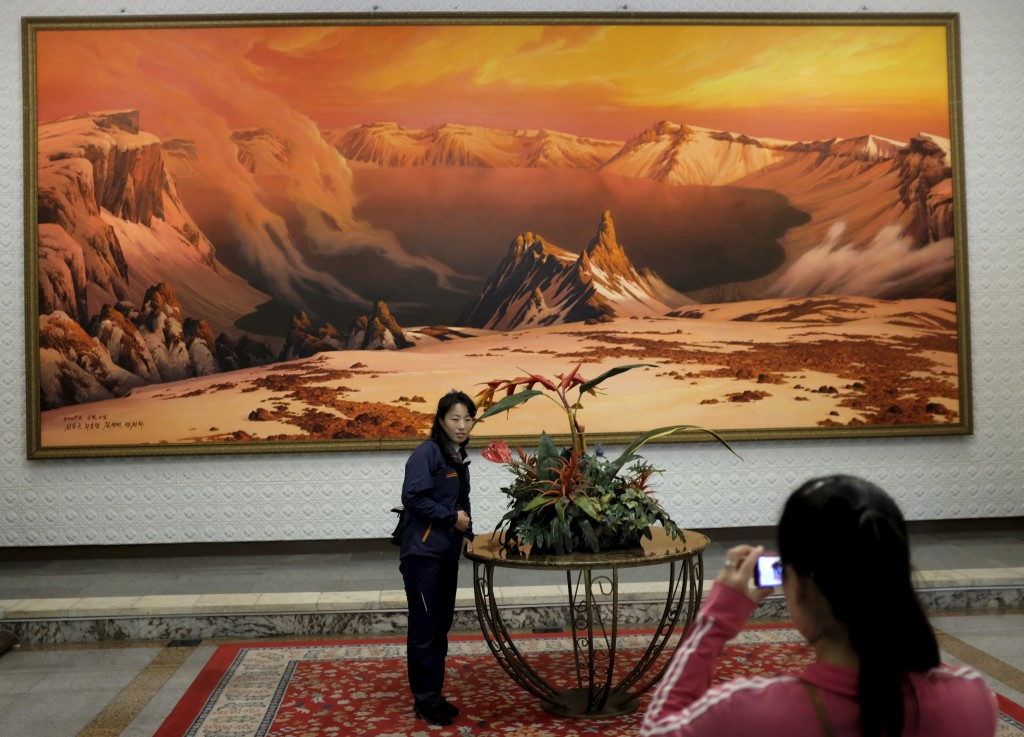 In this Tuesday, Oct. 23, 2018, photo, a woman has her photo taken in front of a painting of the sacred Mount Paektu, in the lobby of the Kumgangsan H