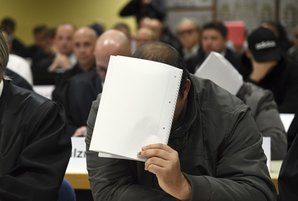 A defandant holds a folder to hide is face at a court in Siegen, Germany, Thursday, Nov. 8, 2018. The court is investigating accusations that guards a
