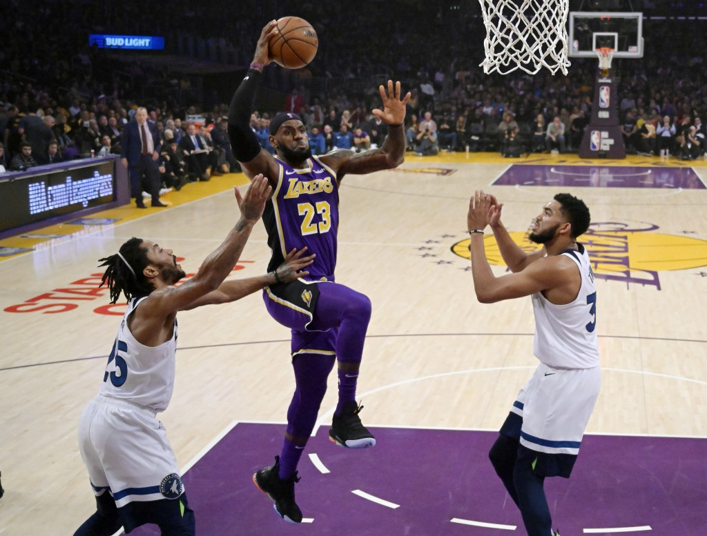 Los Angeles Lakers forward LeBron James, center, shoots as Minnesota Timberwolves guard Derrick Rose, left, and center Karl-Anthony Towns defend durin
