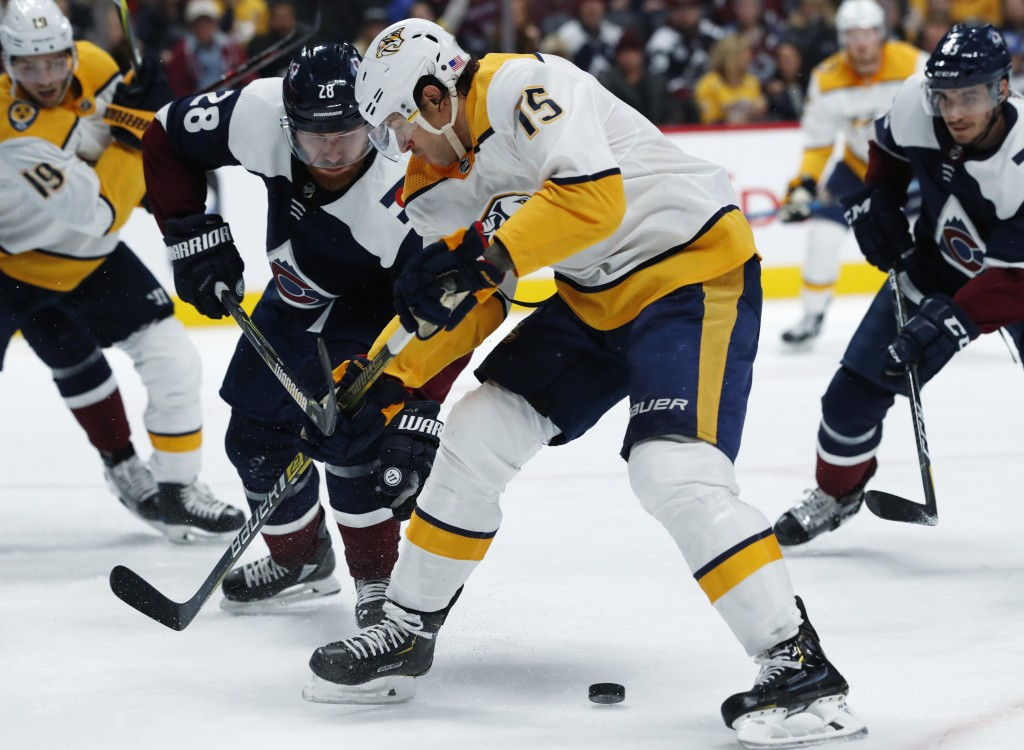 Nashville Predators right wing Craig Smith, right, fights for control of the puck with Colorado Avalanche defenseman Ian Cole during the second period