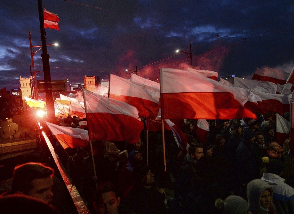 FILE - In this Saturday, Nov. 11, 2017, file photo, Demonstrators burn flares and wave Polish flags during the annual march to commemorate Poland's Na