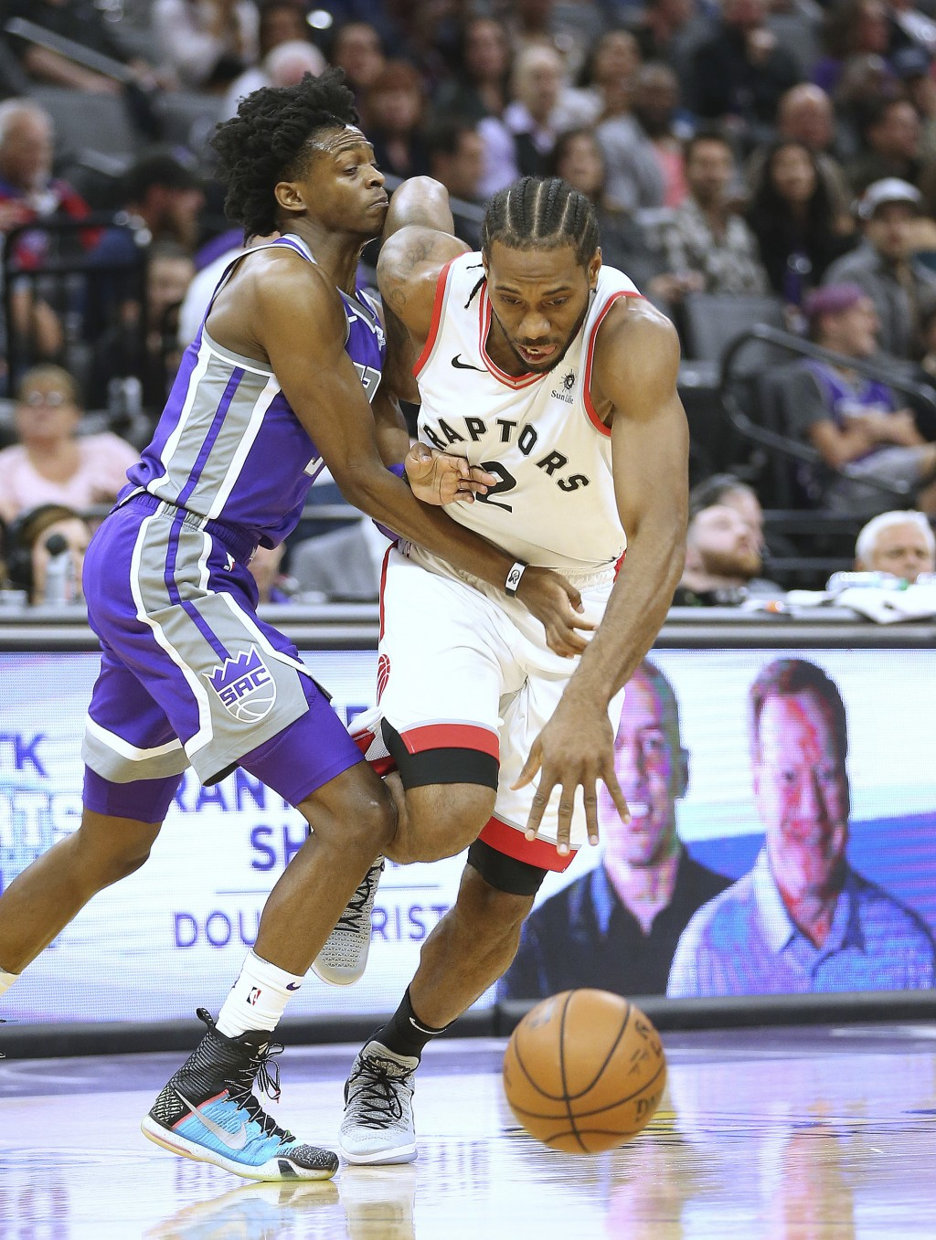 Toronto Raptors forward Kawhi Leonard, right, drives against Sacramento Kings guard De'Aaron Fox during the first quarter of an NBA basketball game We