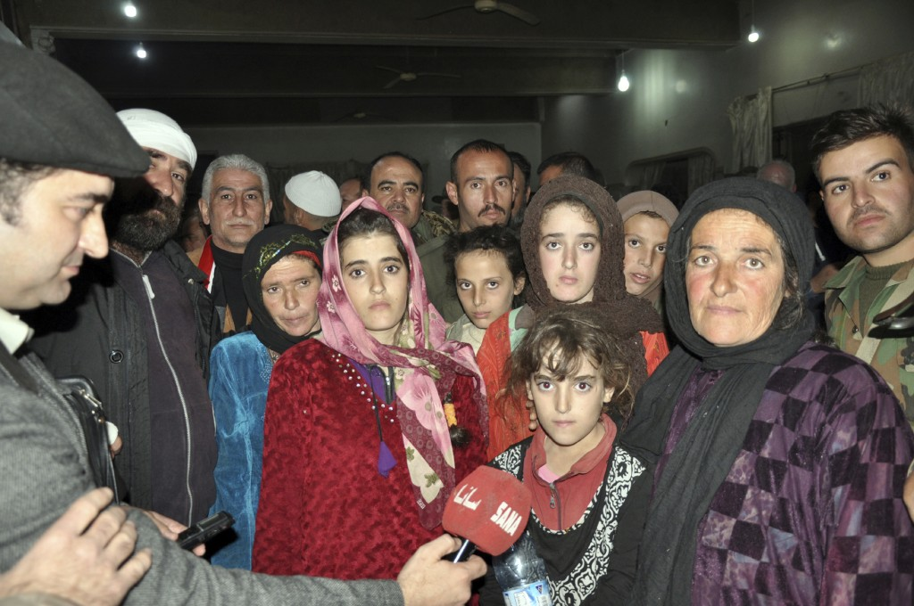 In this photo released by the Syrian official news agency SANA, women and children who were rescued from the Islamic State group in the Hamima area ea