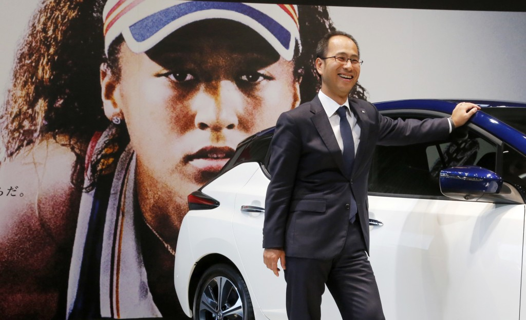 In this Nov. 1, 2018, photo, Masao Tsutsumi, general manager in charge of Osaka-related marketing at Nissan Motor Co., stands with a Leaf electric veh