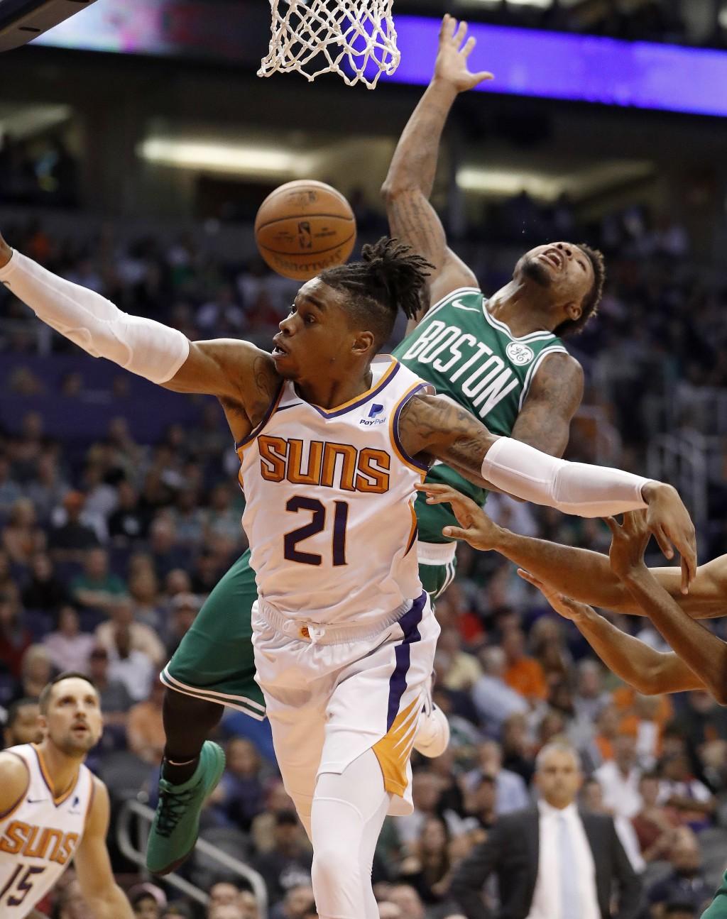 Boston Celtics guard Marcus Smart is fouled by Phoenix Suns forward Richaun Holmes (21) during the first half of an NBA basketball game Thursday, Nov.