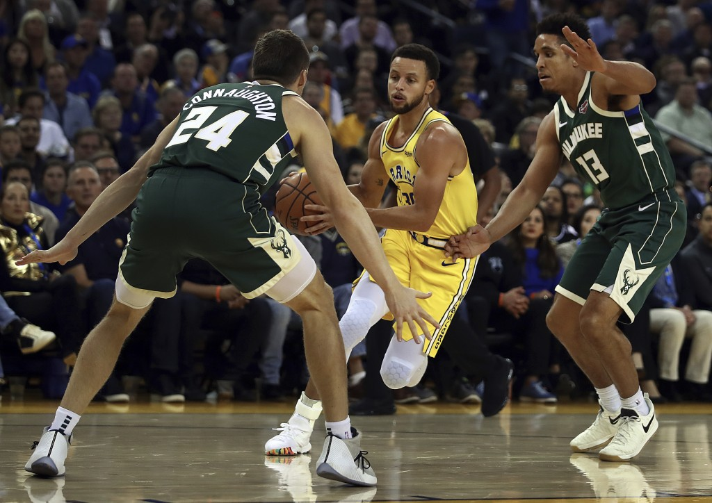 Golden State Warriors' Stephen Curry, center, drives the ball between Milwaukee Bucks' Pat Connaughton (24) and Malcolm Brogdon, right, during the fir