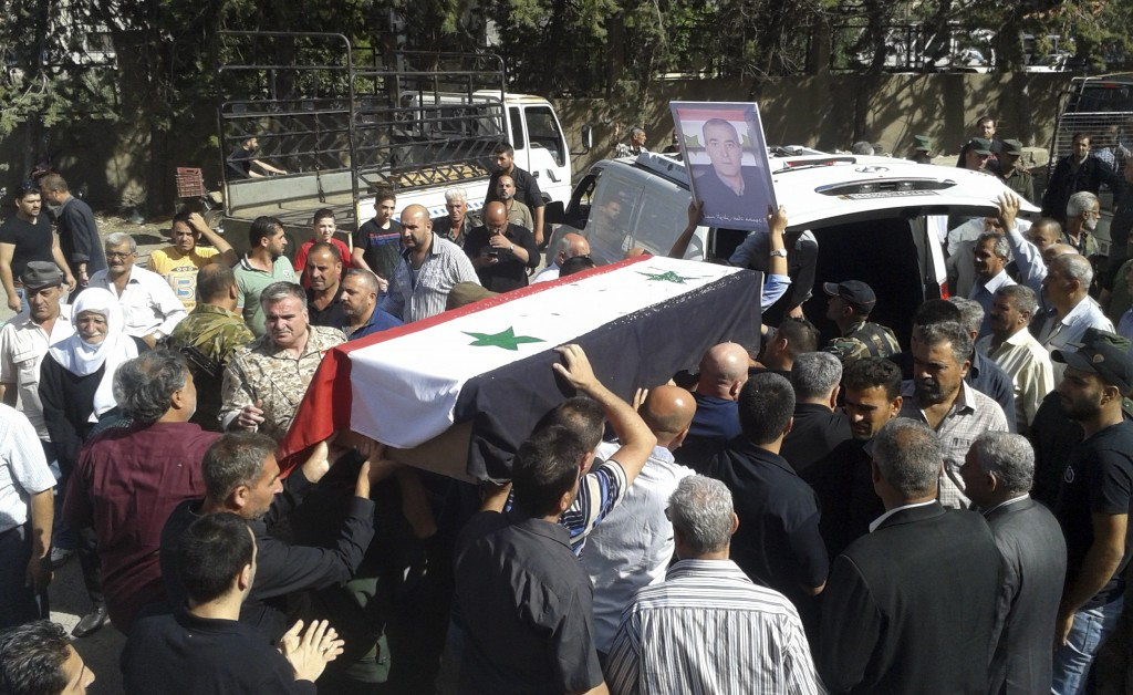 FILE - In this Thursday, July 26, 2018, file photo, released by the Syrian official news agency SANA, mourners carry a coffin of more than 200 people