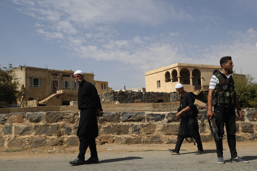 FILE - In this Thursday, Oct. 4, 2018, file photo, young Druze armed men, who carry weapons to defend their village from Islamic State attack, patrol