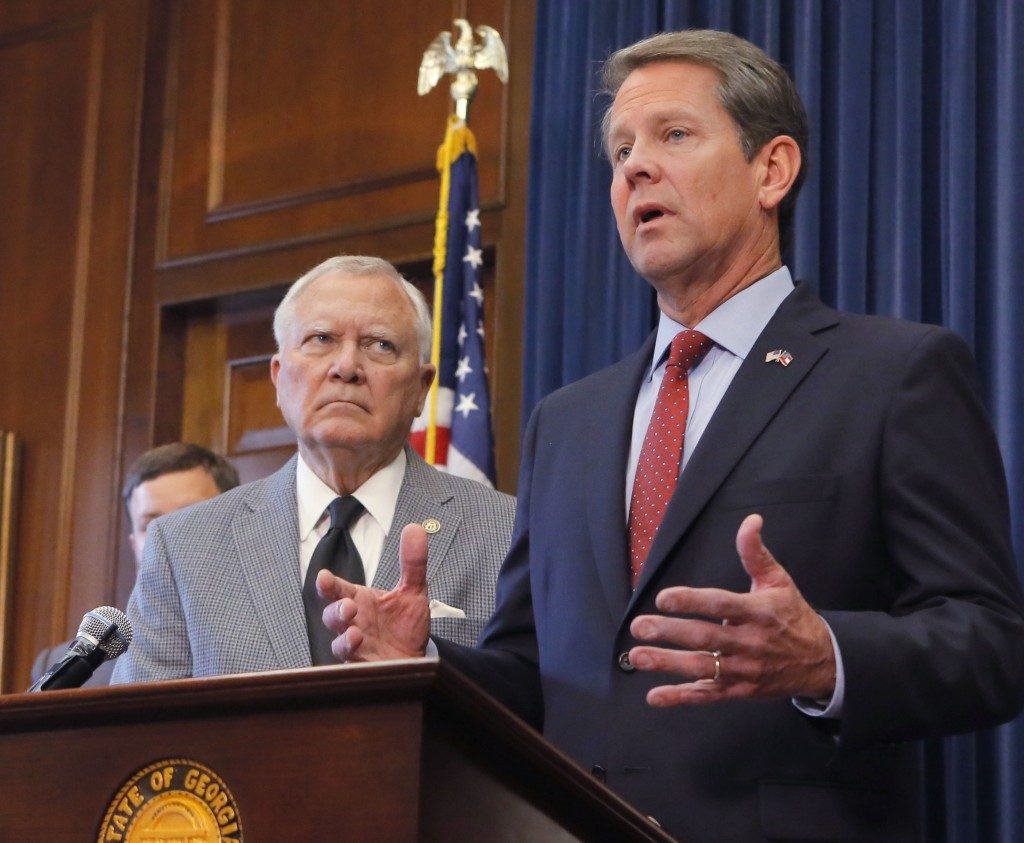 Republican Brian Kemp, right, speaks during a news conference as Georgia Gov. Nathan Deal listens in the Governor's ceremonial office at the Capitol o