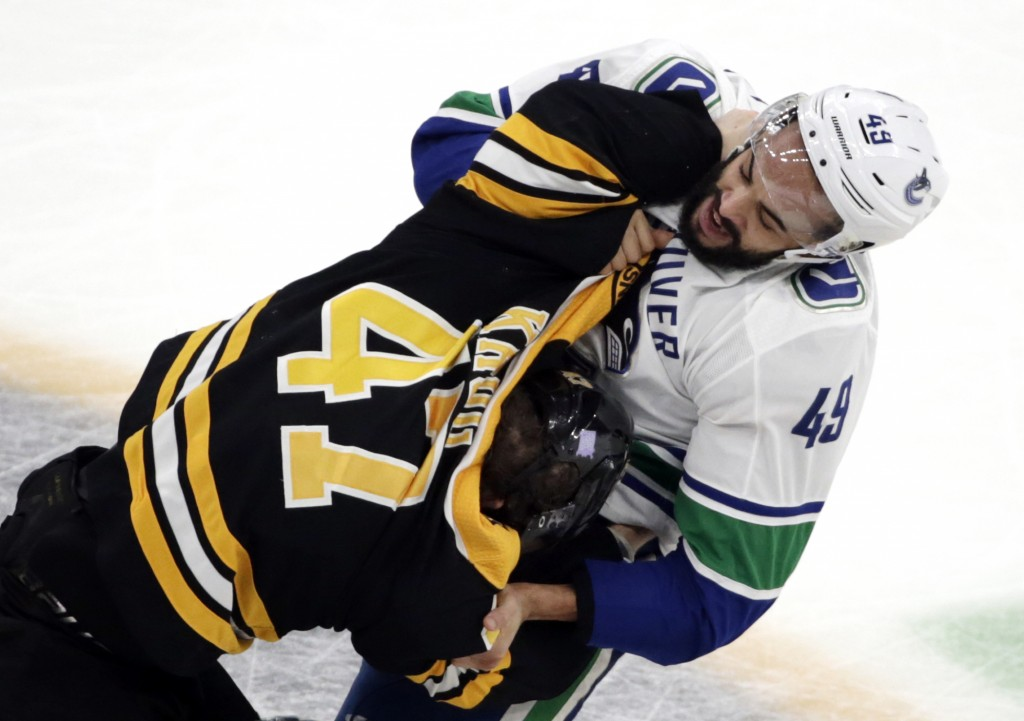 Vancouver Canucks right wing Darren Archibald (49) fights with Boston Bruins defenseman Torey Krug (47) during the third period of an NHL hockey game