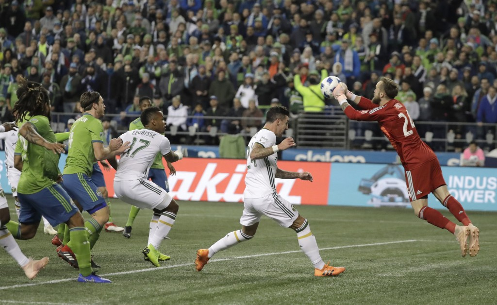 Seattle Sounders goalkeeper Stefan Frei, right, pushes out a ball as Portland Timbers defender Liam Ridgewell, second from left, closes in, during the