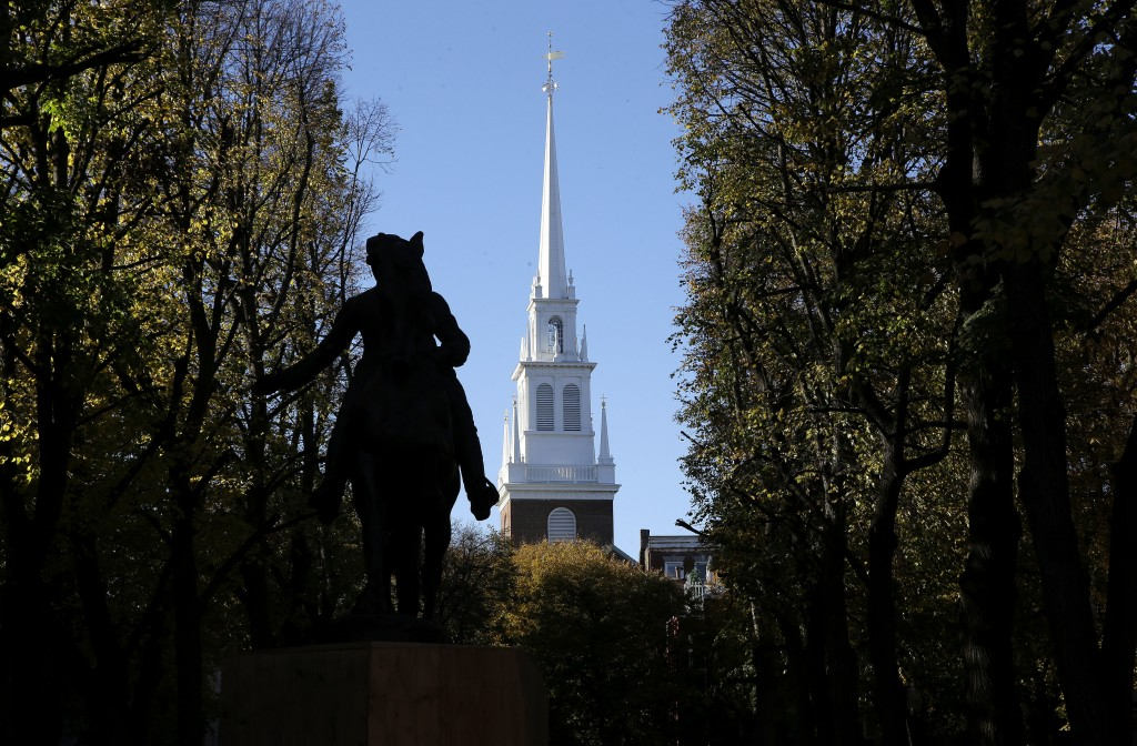 In this Wednesday, Nov. 7, 2018 photo Old North Church stands behind a statue of Paul Revere in the North End neighborhood of Boston. A bronze wreath