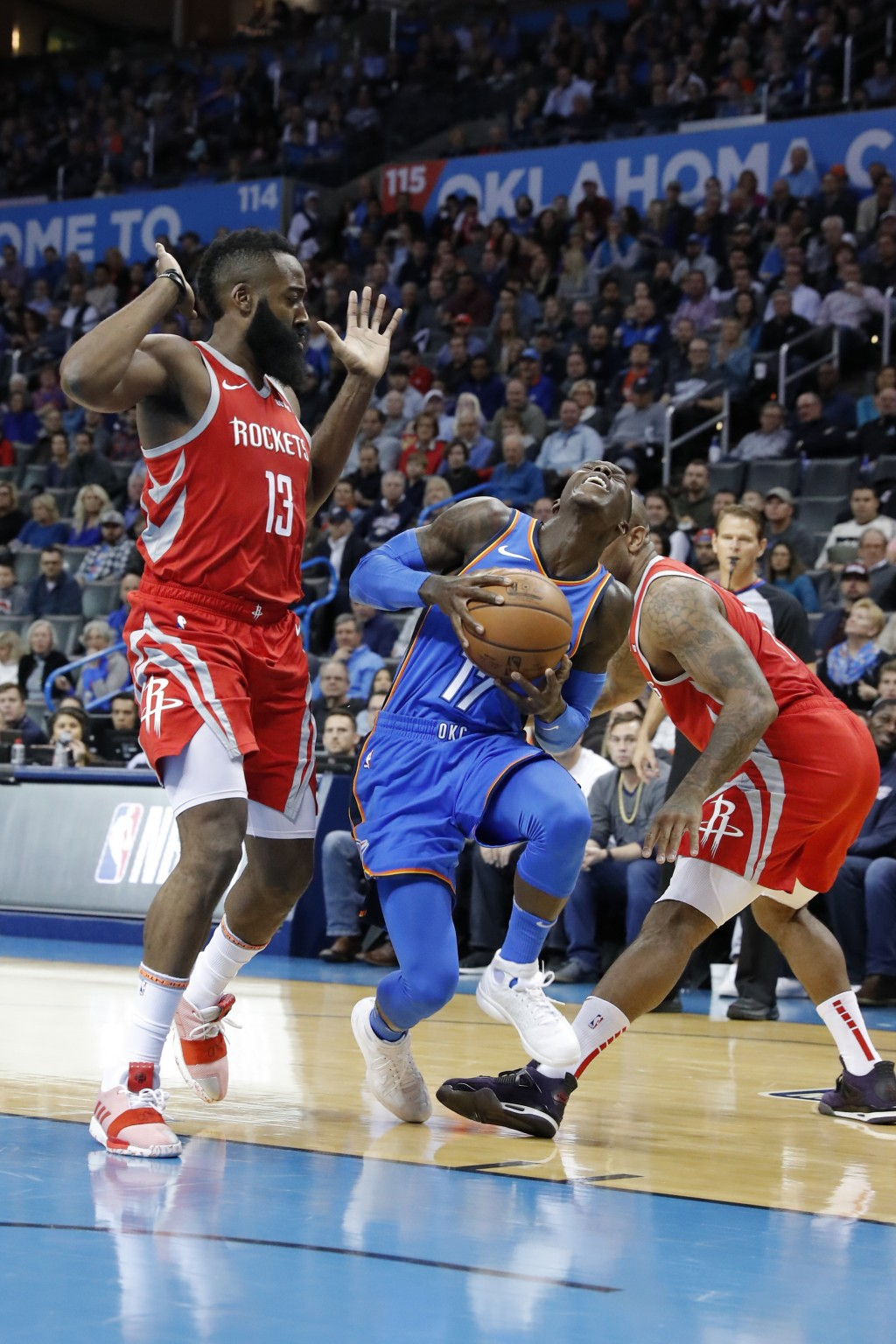 Oklahoma City Thunder forward Paul George (13) drives to the basket between Houston Rockets guard James Harden (13) and forward PJ Tucker (17) during