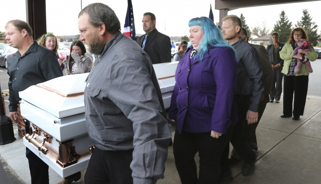 Judy Schneider of Chippewa Falls, the grandmother of Haylee Hickle and mother of Sara Schneider clutches a bear as the casket, holding them both is ca