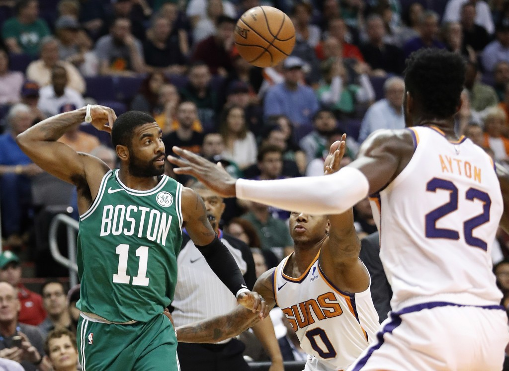 Boston Celtics guard Kyrie Irving (11) throws a pass over Phoenix Suns guard Isaiah Canaan (0) during the first half of an NBA basketball game Thursda