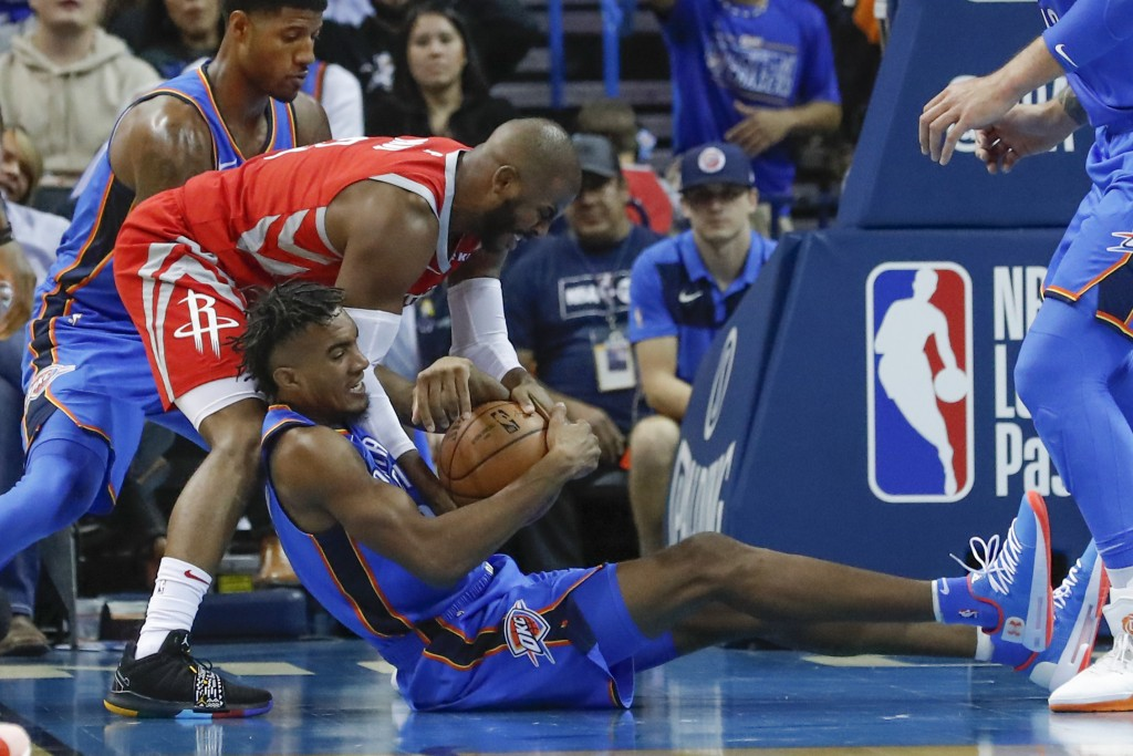 Oklahoma City Thunder guard Terrance Ferguson, bottom, and Houston Rockets guard Chris Paul, top, compete for a loose ball during the first half of an