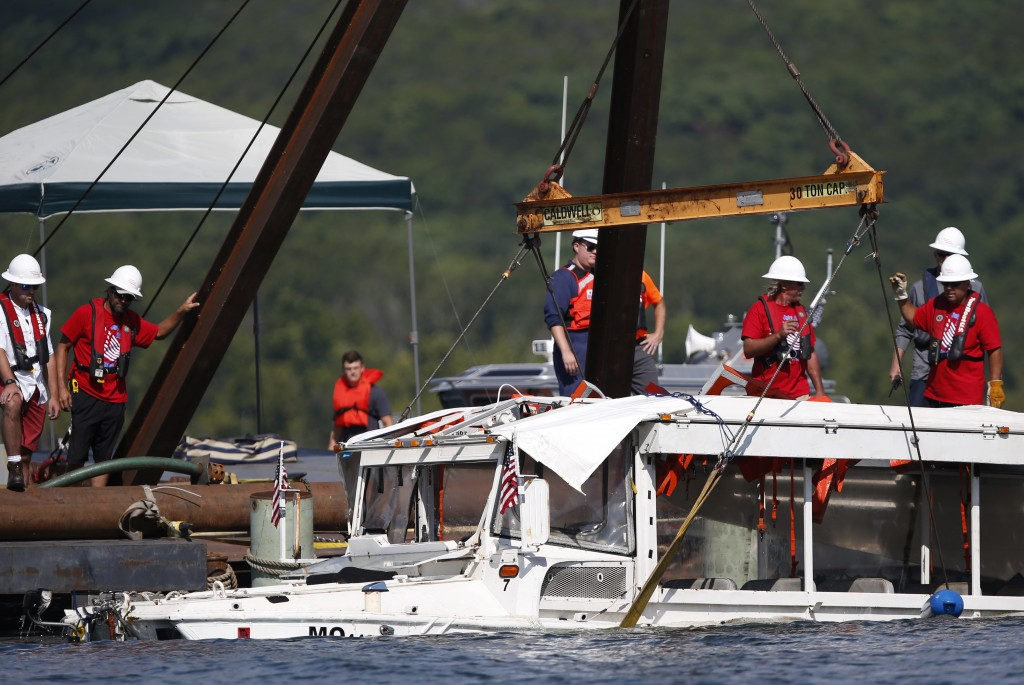FILE - In this July 23, 2018 file photo, a duck boat that sank in Table Rock Lake in Branson, Mo., is raised after it went down the evening of July 19...
