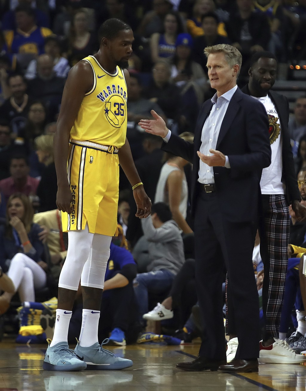 Golden State Warriors coach Steve Kerr, right, speaks with Kevin Durant during the first half of the team's NBA basketball game against the Milwaukee