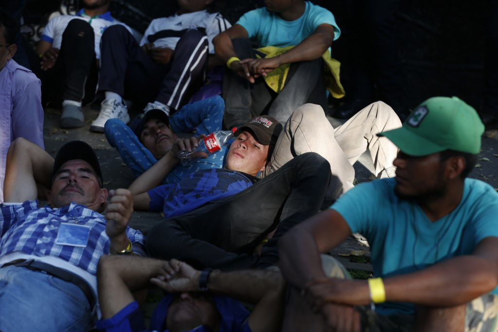 Scores of Central American migrants, representing the thousands participating in a caravan trying to reach the U.S. border, rest in front of the offic