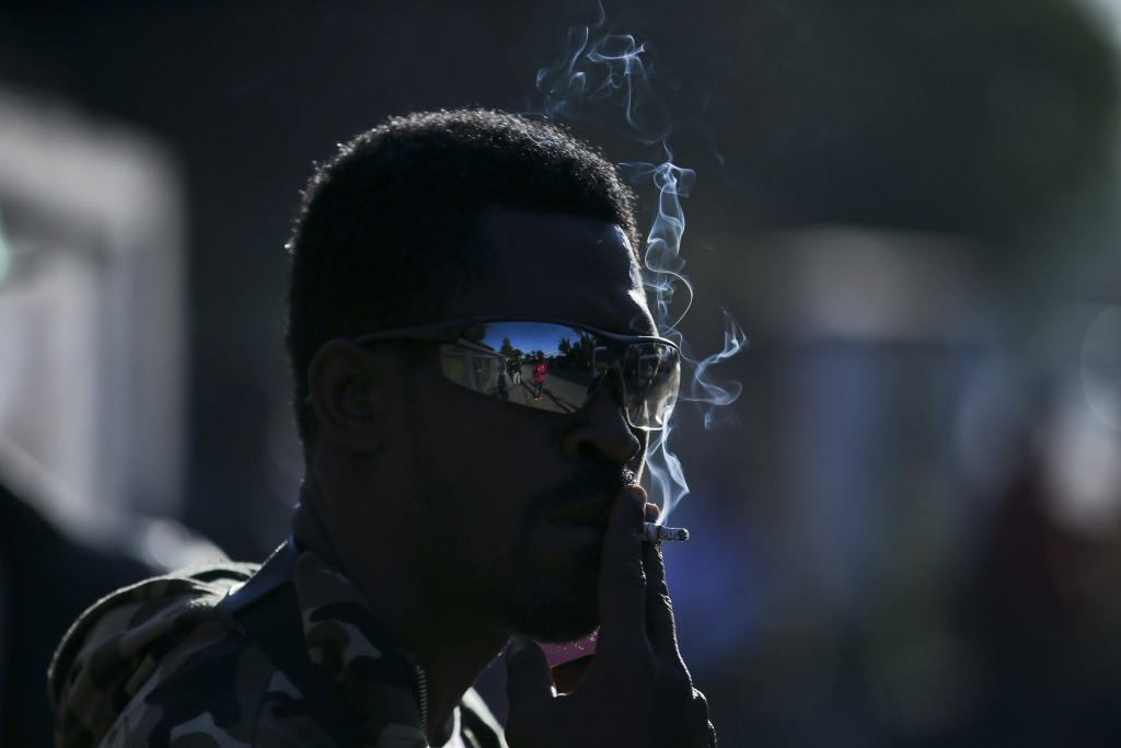 In this Nov. 7, 2018 photo, a Haitian migrant smokes a cigarette as he waits to register for repatriation, in Santiago, Chile. After an unsuccessful m