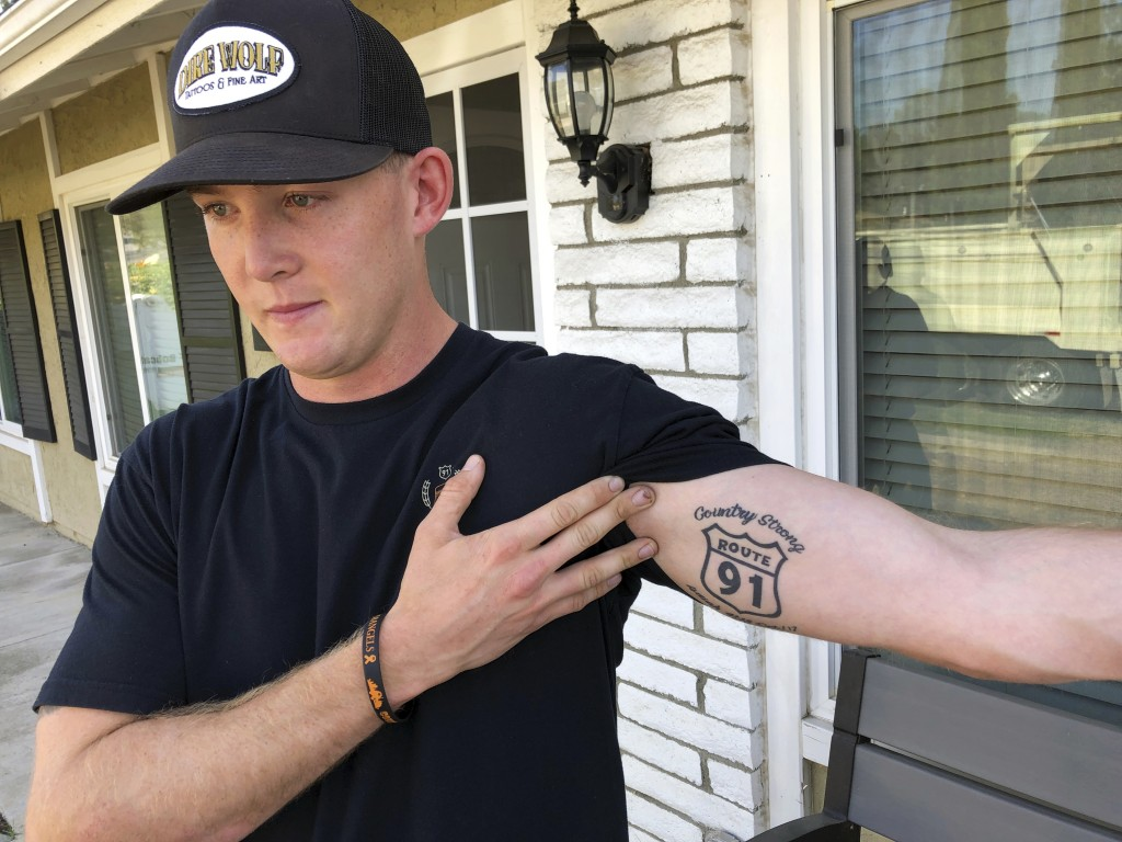 Brendan Kelly speaks with reporters outside his home, as he shows his Route 91 tattoo, Thursday, Nov. 8, 2018, in Thousand Oaks, Calif. Kelly, a Marin