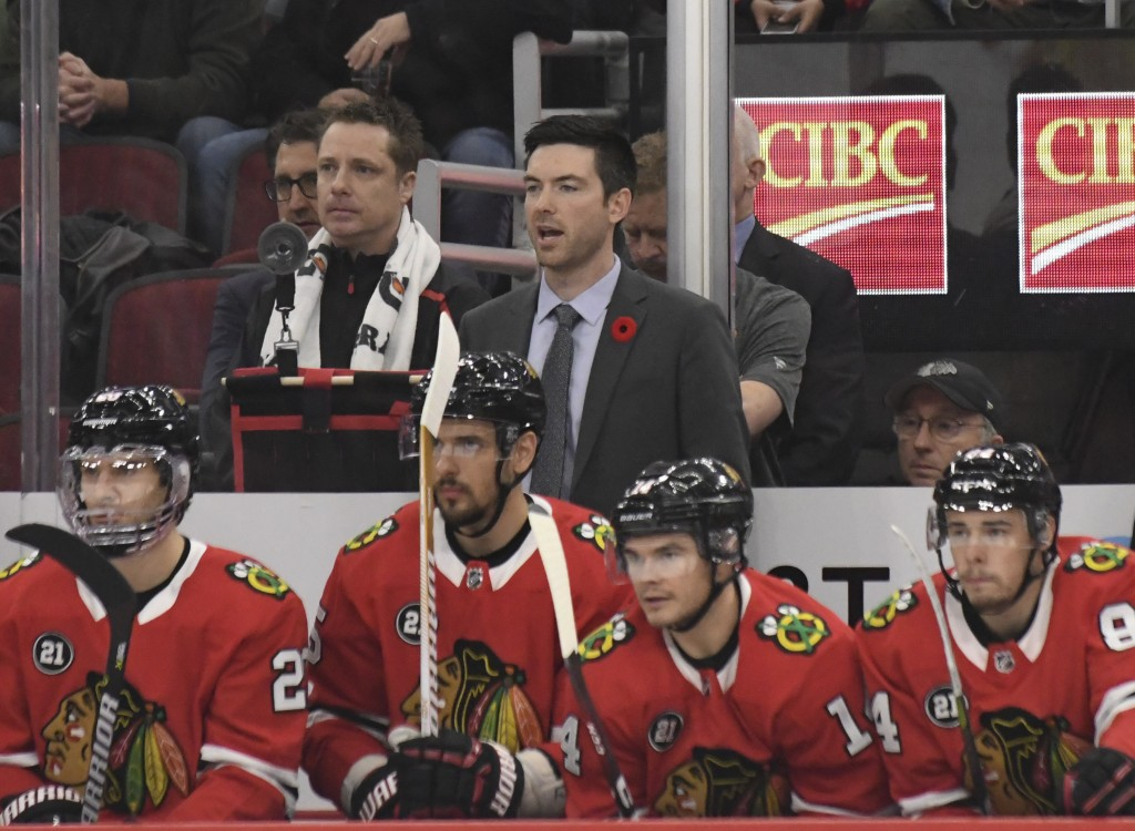 Chicago Blackhawks head coach Jeremy Colliton, center, watches play during the first period of an NHL hockey game against the Carolina Hurricanes Thur