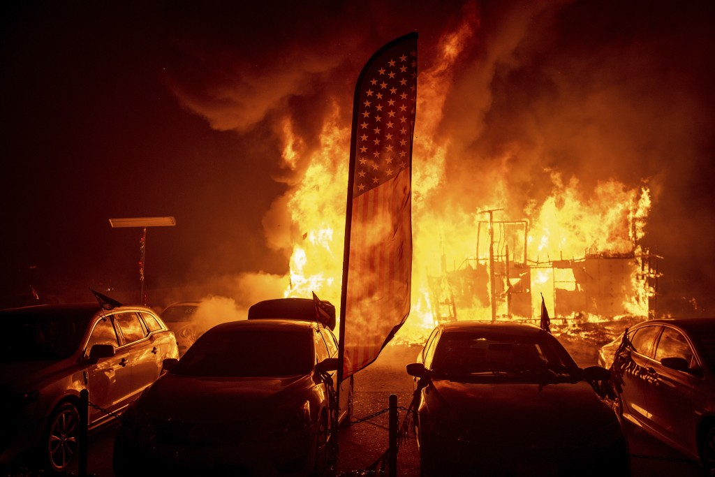 Flames consume a car dealership as the Camp Fire tears through Paradise, Calif., on Thursday, Nov. 8, 2018. Tens of thousands of people fled a fast-mo