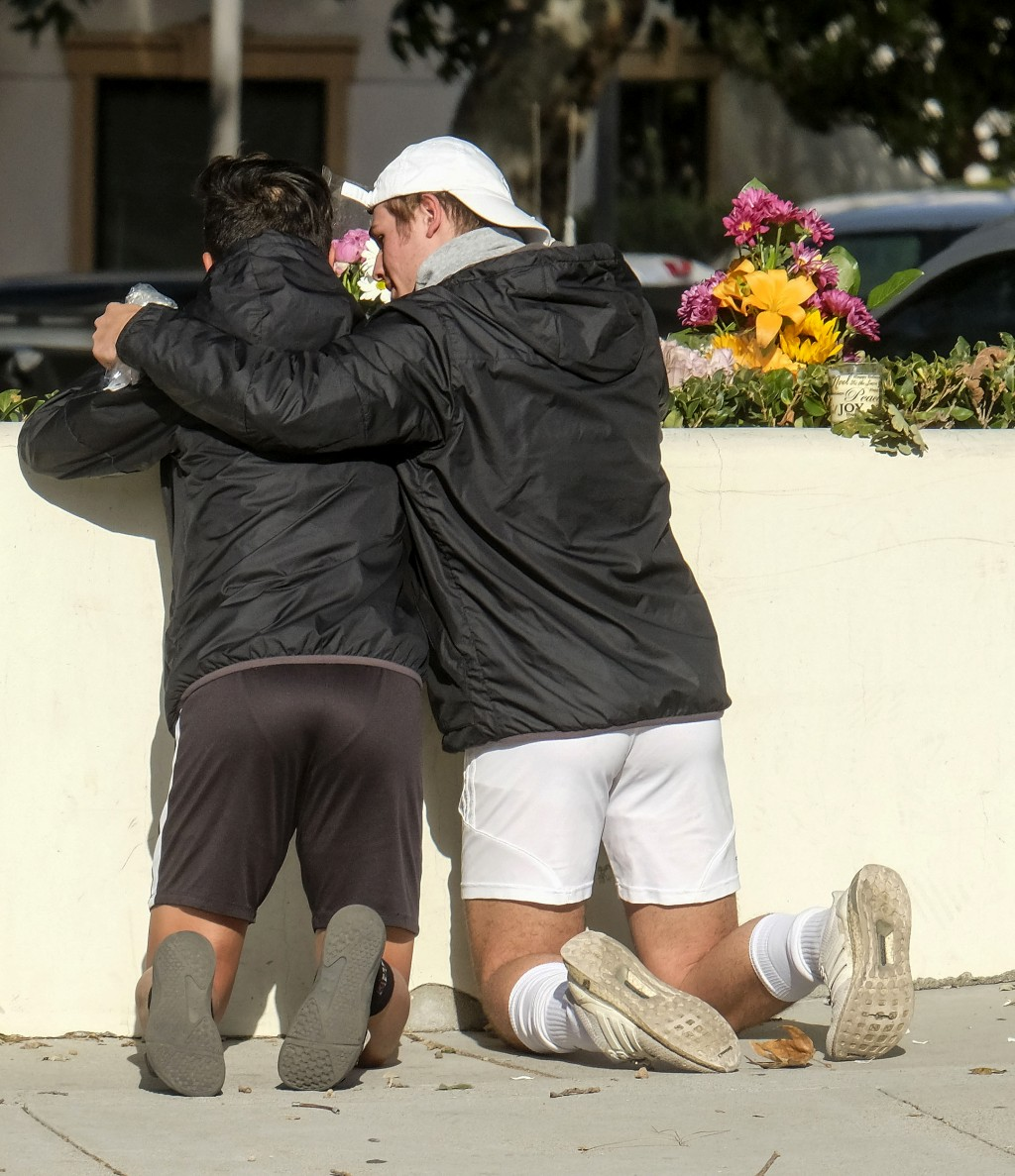 People place flowers near the scene of a mass shooting Thursday, Nov. 8, 2018, in Thousand Oaks, Calif., after a gunman opened fire Wednesday evening