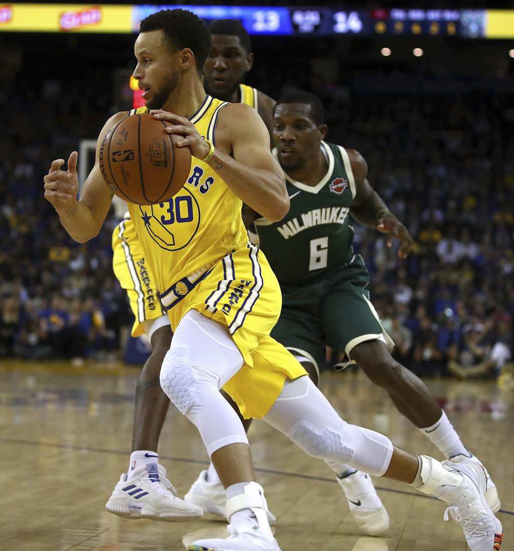Golden State Warriors' Stephen Curry drives the ball past Milwaukee Bucks' Eric Bledsoe (6) during the first half of an NBA basketball game Thursday,