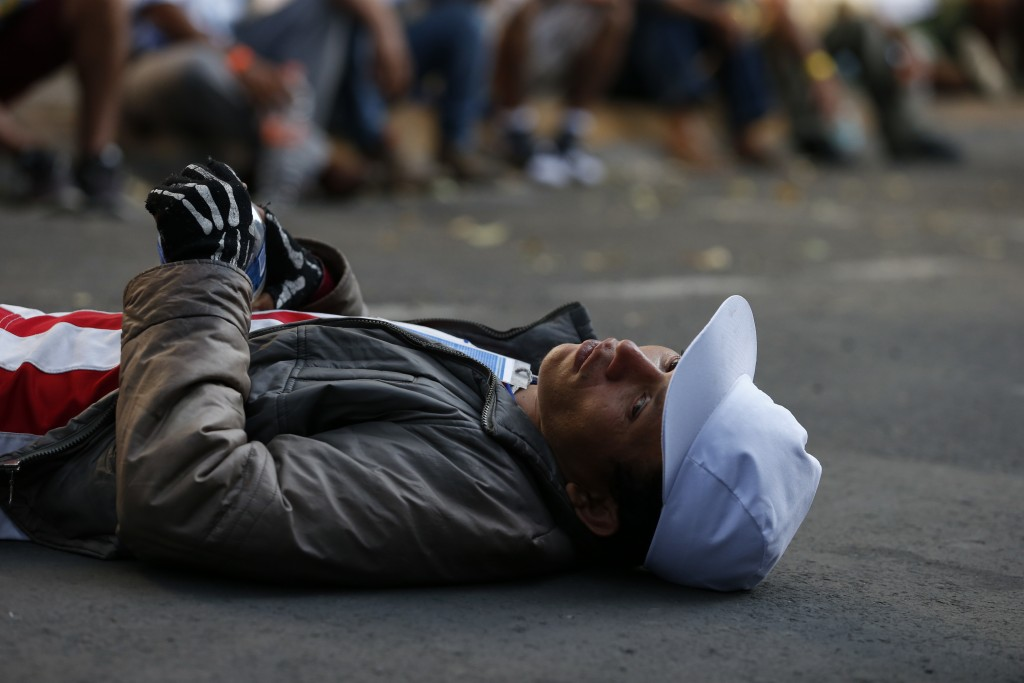 A man rests on the street after scores of Central American migrants, representing the thousands participating in a caravan trying to reach the U.S. bo
