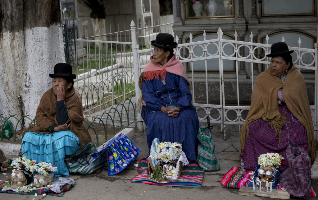 In this Nov. 8, 2018 photo, women sit with their decorated human skulls at the at the General Cemetery during the Natitas Festival, in La Paz, Bolivia