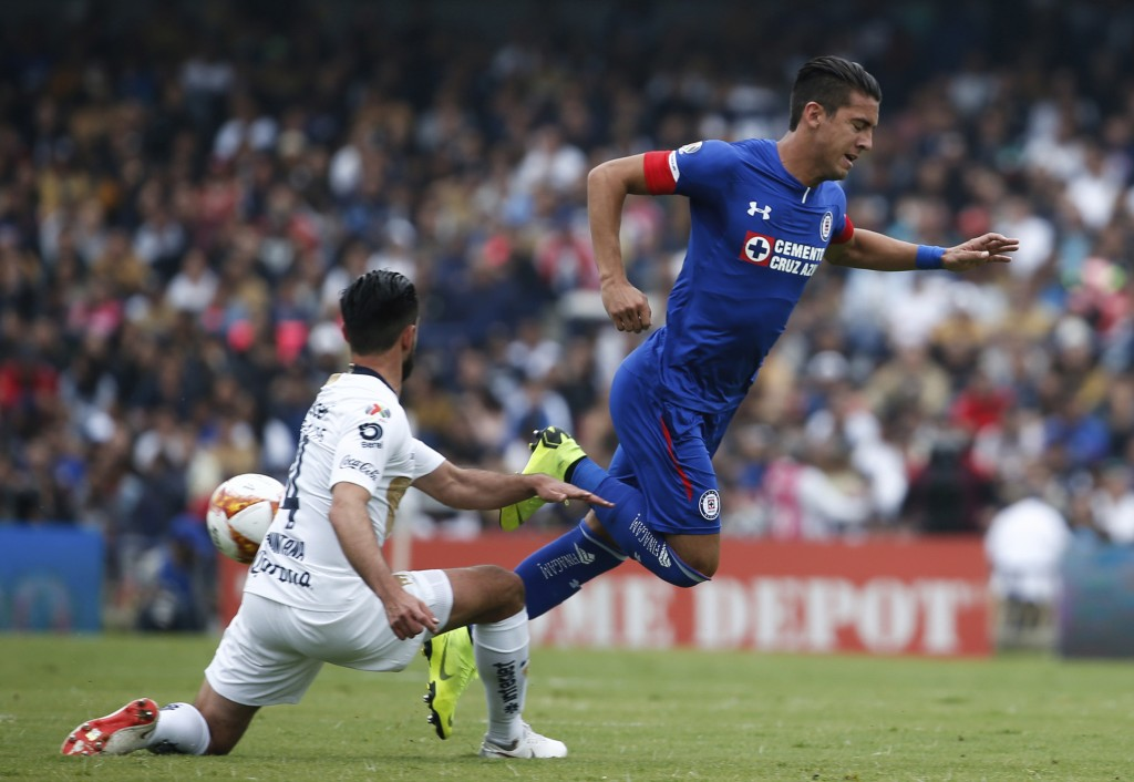 In this Nov. 4, 2018 photo, Puma's defender Luis Quintana, left, slides to stop Cruz Azul's midfielder Javier Salas during a Mexico soccer league matc