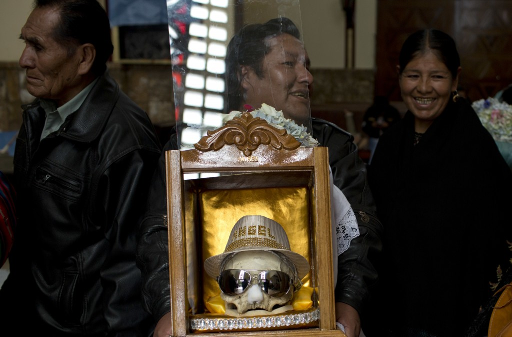 A man carries a decorated human skull after praying at the General Cemetery chapel during the Natitas Festival in La Paz, Bolivia, Thursday, Nov. 8, 2...