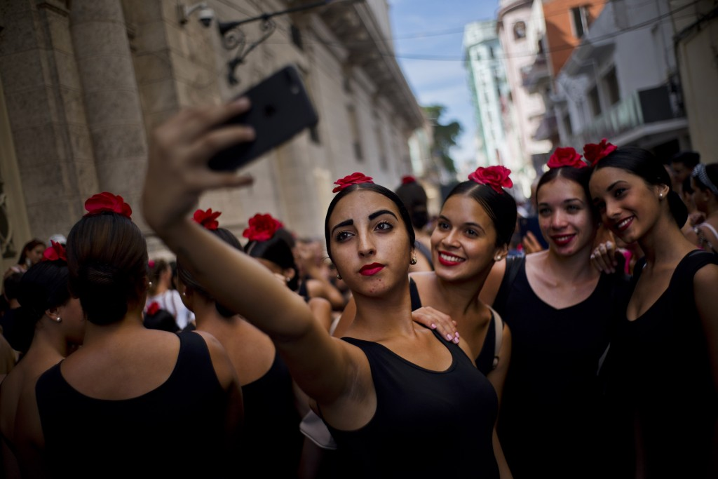 In this Nov. 4, 2018 photo, young flamenco dancers take a selfie before performing in the street during the 26th International Ballet Festival in Hava