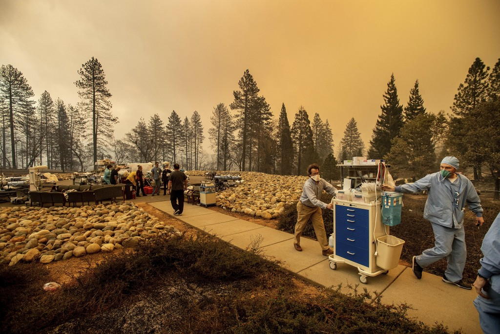 Medical workers move equipment from a makeshift emergency room while the Feather River Hospital burns as the Camp Fire rages through Paradise, Calif.,