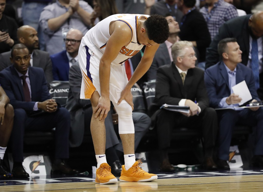 Phoenix Suns guard Devin Booker looks at the floor as time expires during the second half of the team's NBA basketball game against the Boston Celtics