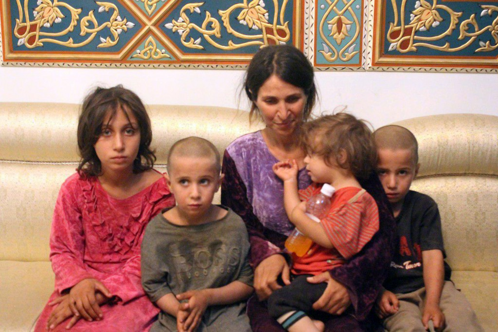FILE - In this Thursday, July 26, 2018, file photo, released by the Syrian official news agency SANA, Abeer Shalgheen and her four children after bein