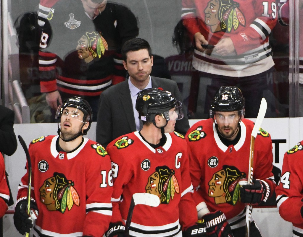 Chicago Blackhawks head coach Jeremy Colliton, center, watches play during the second period of an NHL hockey game against the Carolina Hurricanes Thu