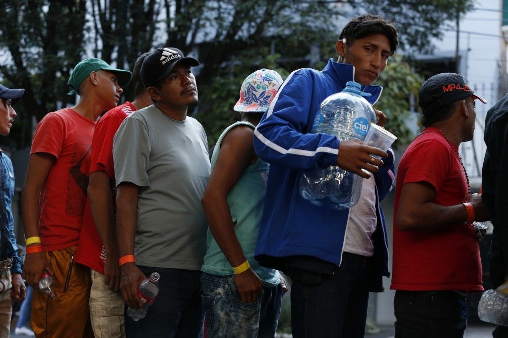 Men line up for donated drinking water, after scores of Central American migrants, representing the thousands participating in a caravan trying to rea