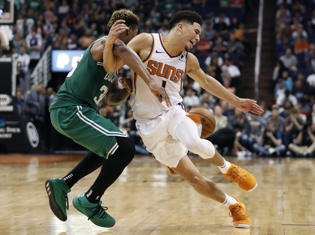 Phoenix Suns guard Devin Booker (1) is fouled by Boston Celtics guard Marcus Smart during the second half of an NBA basketball game Thursday, Nov. 8,