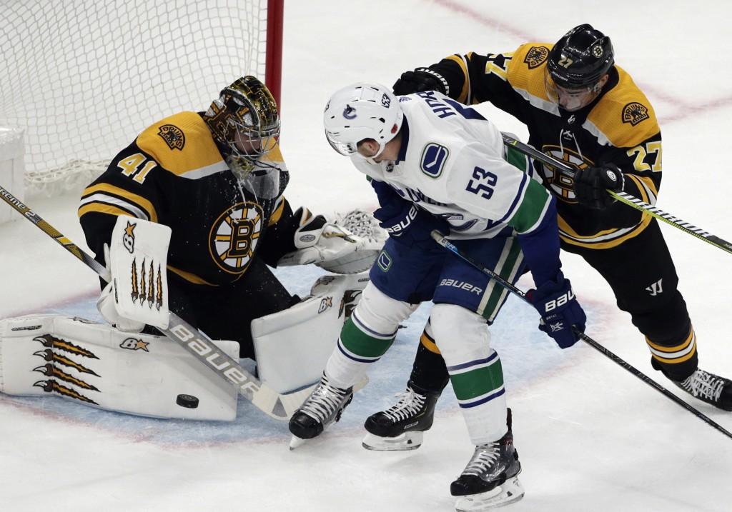 Boston Bruins defenseman John Moore (27) checks Vancouver Canucks center Bo Horvat (53) as Bruins goaltender Jaroslav Halak (41) makes a pad save duri