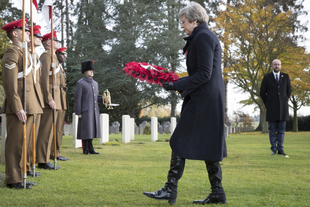 British Prime Minister Theresa May, center, and Belgian Prime Minister Charles Michel, right, lay wreaths at the graves of British World War I soldier...