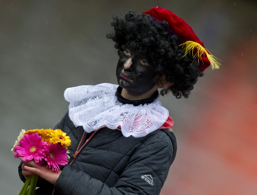 In this Saturday, Nov. 18, 2017, file photo, a child dressed as Black Pete waits for the arrival of Sinterklaas, in Dokkum, northern Netherlands. A co