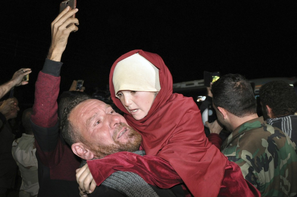 In this photo released by the Syrian official news agency SANA, a man holds an young girl who has been rescued from the Islamic State group in the Ham