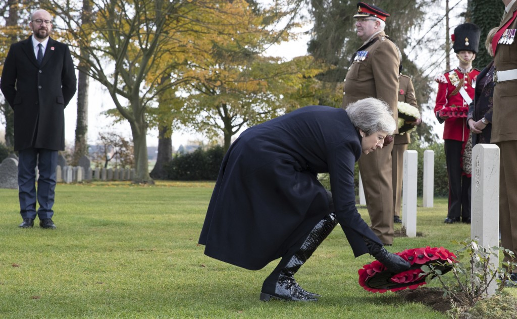 British Prime Minister Theresa May, center, and Belgian Prime Minister Charles Michel, left, lay wreaths at the graves of British World War I soldiers...