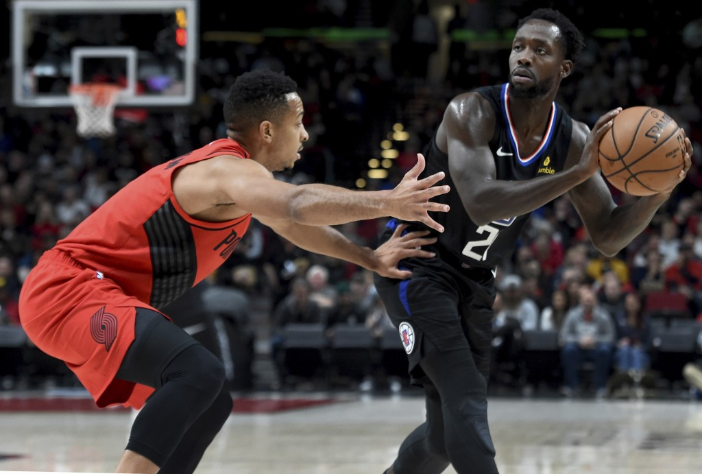 Los  Angeles Clippers guard Patrick Beverley, right, looks to pass the ball on Portland Trail Blazers guard CJ McCollum, left, during the first half o