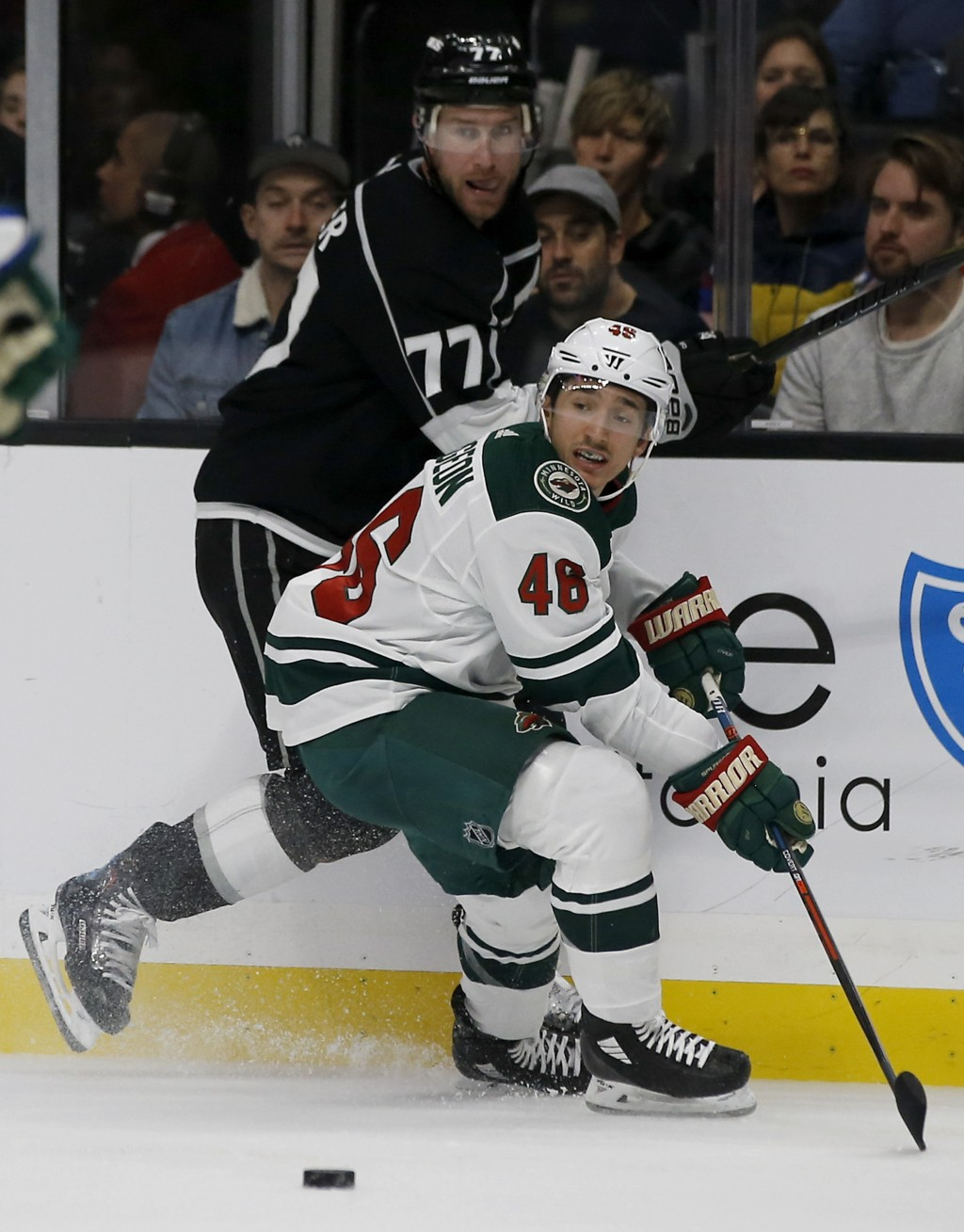 Minnesota Wild defenseman Jared Spurgeon (46) takes the puck away from Los Angeles Kings center Jeff Carter (77) during the second period of an NHL ho