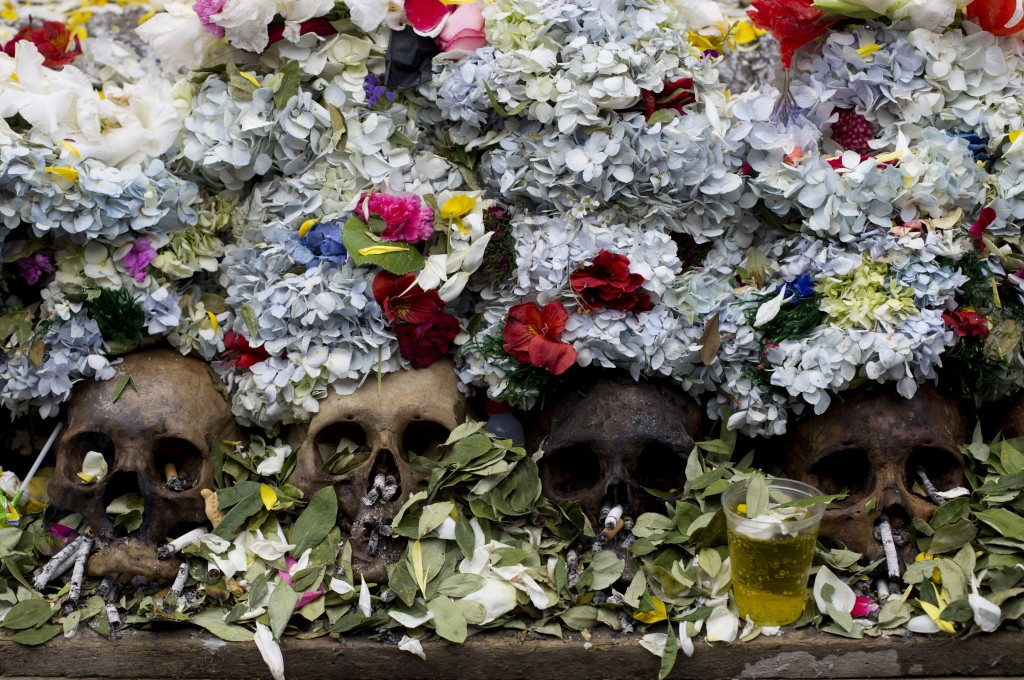 "Human skulls or ""natitas"" crowned with flowers are surrounded by offerings of coca leaves, flower petals and cigarettes, at the General Cemetery marki"