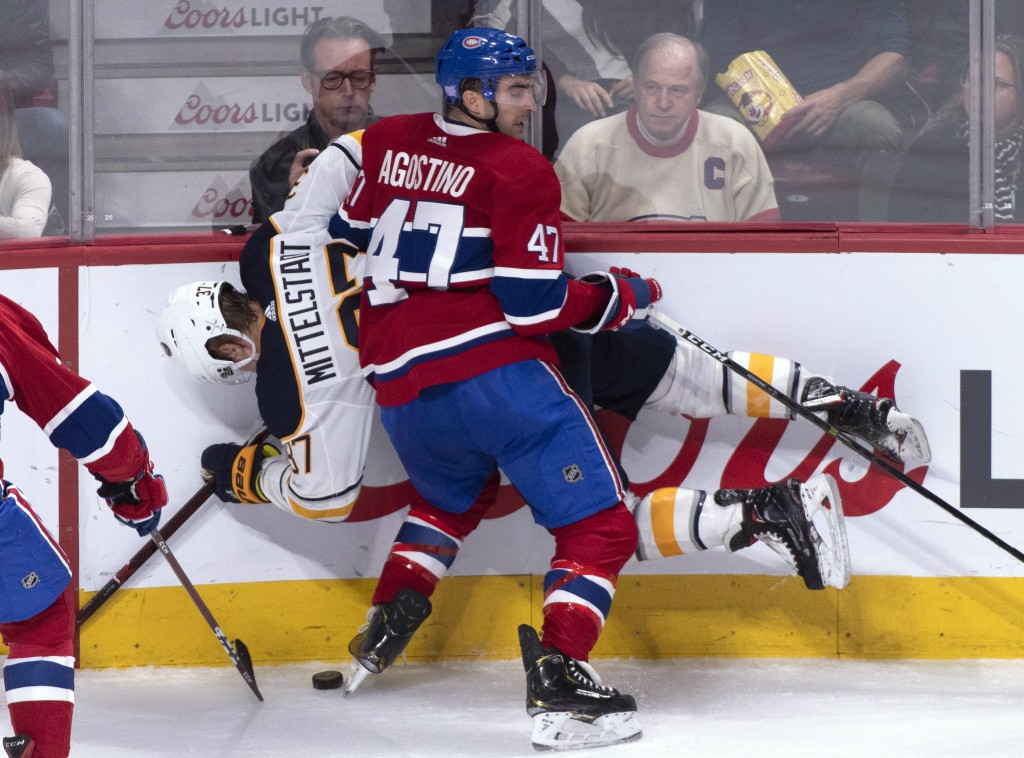 Buffalo Sabres' Casey Mittelstadt is checked into the boards by Montreal Canadiens' Kenny Agostino during the second period of an NHL hockey game Thur
