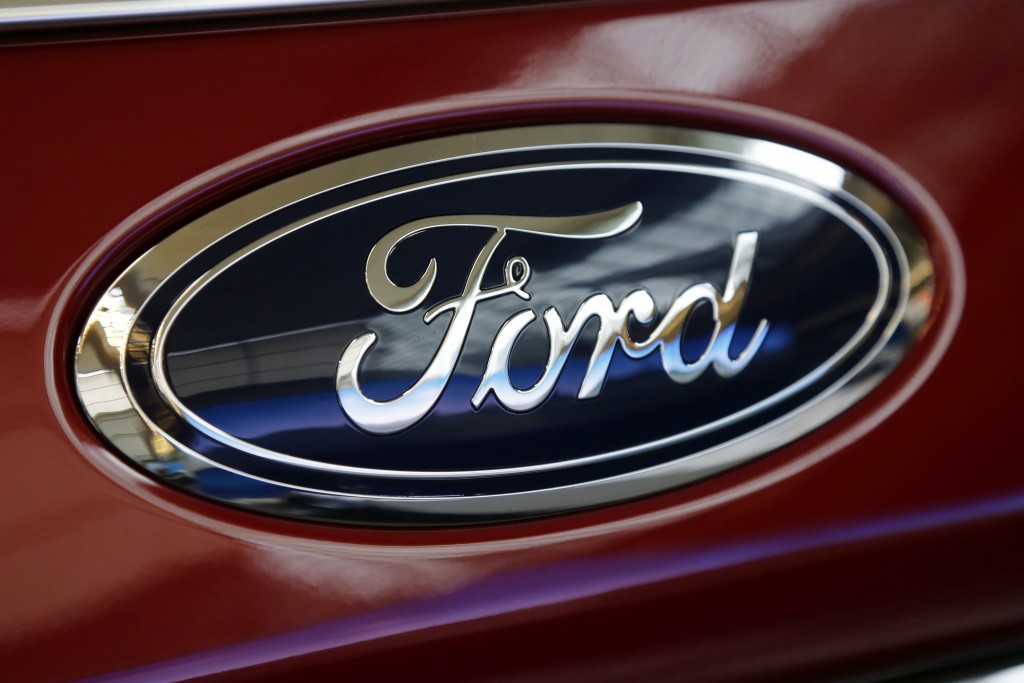 FILE- This Feb. 15, 2018, file photo shows a Ford logo on a vehicle at the Pittsburgh Auto Show in Pittsburgh. Ford Motor Co. has bought an electric s